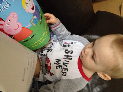 Blake in his PJ's reading his copy of Penwizard personalised story book - Peppa pig comes to your child's birthday party