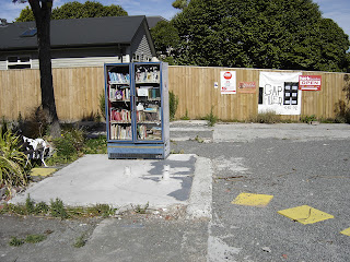A fridge full of books sits on an empty lot, a bench to one side beneath two small trees, surrounded by gravel and the remains of concrete foundations