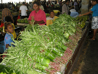 people and leafy vegetables at market