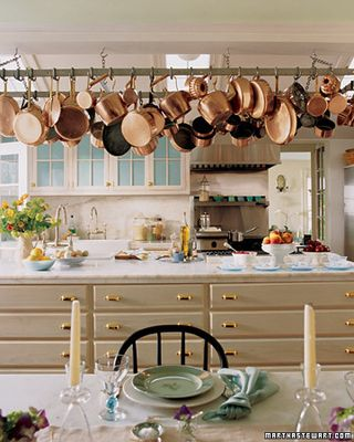 Traditional Cream Kitchen With Marble Counter Tops And Copper Pots Hanging Above The Island