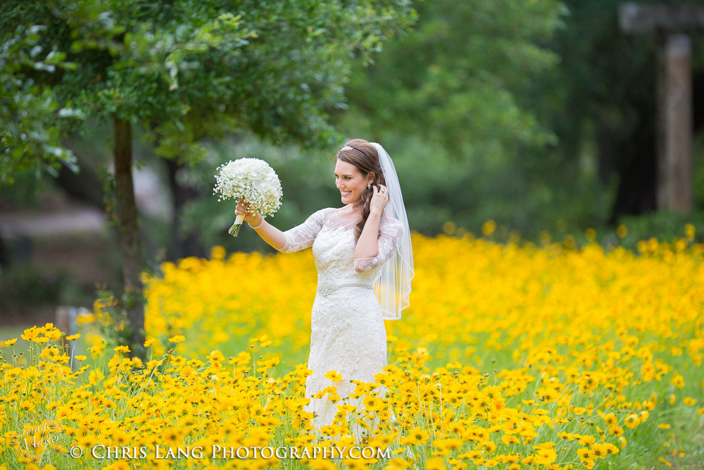 Airlie Gardens- Bride Looking at her wedding bouquet while standing a field of yellow flowers.  Bridal-inspiration-ideas