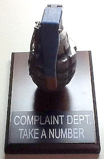 "Novelty Grenade on plaque that states: ""CompaintDept. Take a Number."""