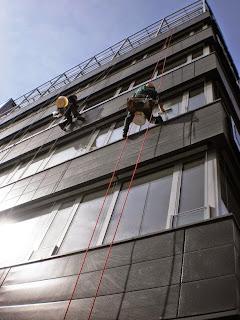 Umývání oken výškových budov provádějí horolezci