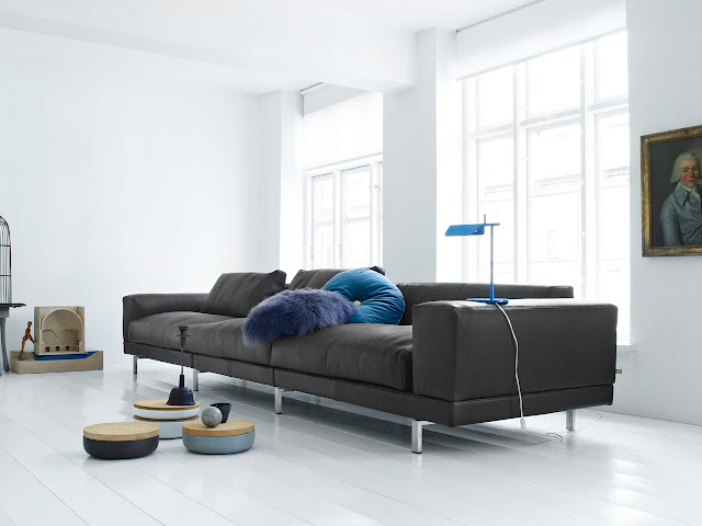 simple black low back sofa with white decoration and painting in the wall