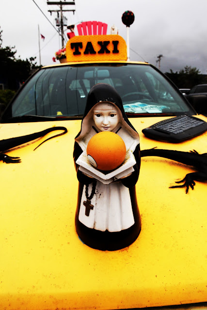 A taxi in Cannon Beach covered in art including a nun as a hood ornament and two iguanas.