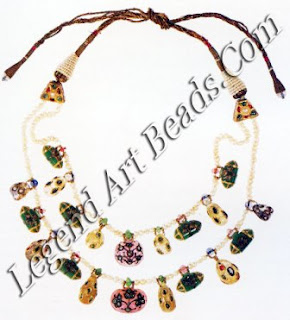 Moonstones, tourmalines, sapphires and aventurines are inlaid with diamonds, rubies and emeralds, and strung with emerald and sapphire beads on two strands of small pearls.