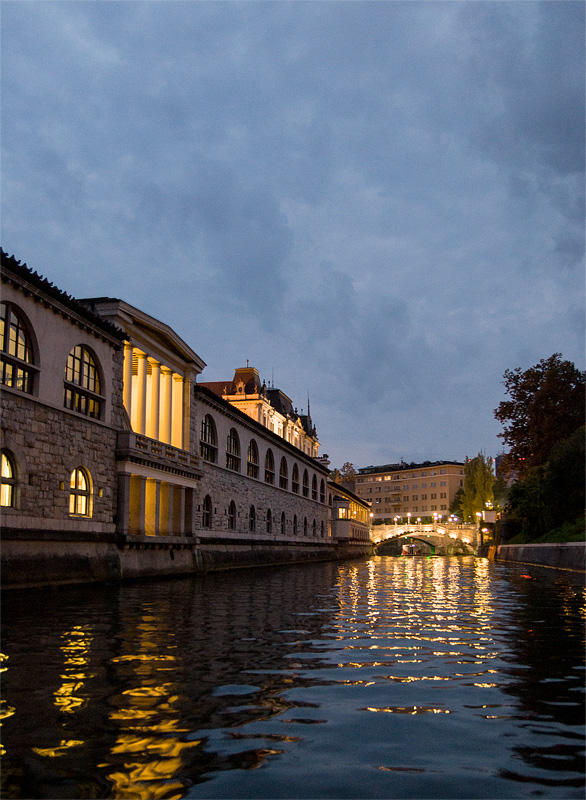 Ljubljana iz rečnega korita Plečnikove arkade zvečer full