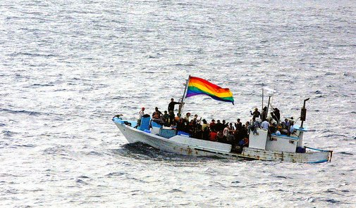 A boat of asylum seekers, carrying a rainbow flag.
