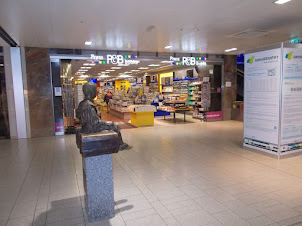 """Book shop and statue of a boy in """"Westbahnhoff railway station mall"""""""