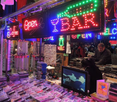 Neon signs and phone covers in an indoor market