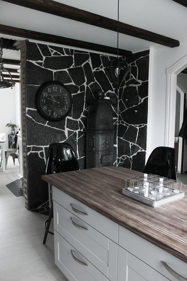 kök, stensatt vägg, sten bakom kamin, köksö, bänkskiva på köksö, stor svart klocka, köksklocka, vitt och grått kök, inredning kök, inspiration kök