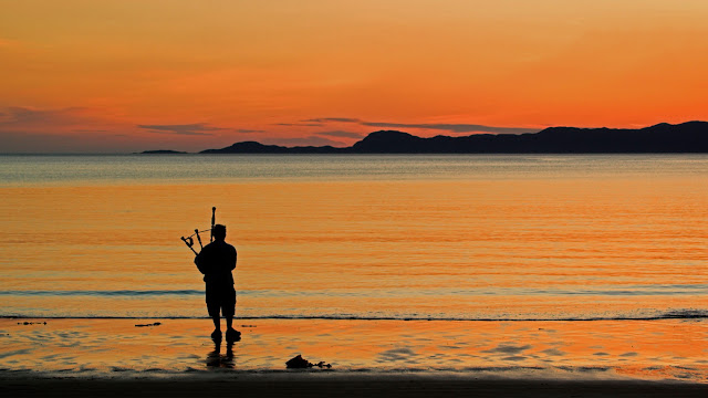 A bagpiper on Arisaig beach in Scotland (© ColsTravel/Alamy)