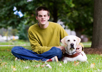 John Pastorius, seated on grass with dog guide