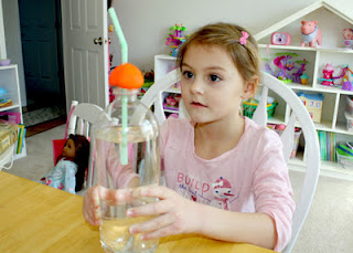 "Using a clear plastic bottle filled with water, a straw and modeling clay, we created a model of a lung. The plastic bottle served as the lung, the water as air, and the straw as a bronchial tube. When Tessa squeezed the ""lung,"" the ""air"" was forced out through the ""bronchial tube"" to mimic exhalation. Releasing the lung created the reverse effect...inhalation."