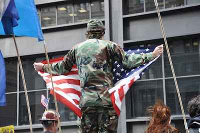 Photograph of a man wearing camouflage fatigues and  holding an American flag
