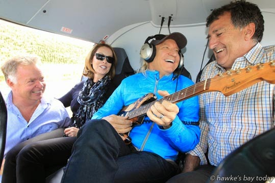 L-R: Joe Faram, pilot, owner, Joe Faram Aviation Group, Bridge Pa, Hastings; Marjorie Walsh, Joe Walsh, with Joe Faram's guitar which he autographed; Andy Lowe, host - pictured in Joe Faram's Squirrel B3 helicopter at Andy's bach at Ocean Beach. photograph