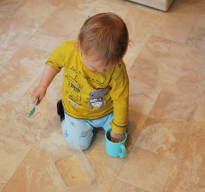 toddler sat on floor with cup, spoon and pearl barley