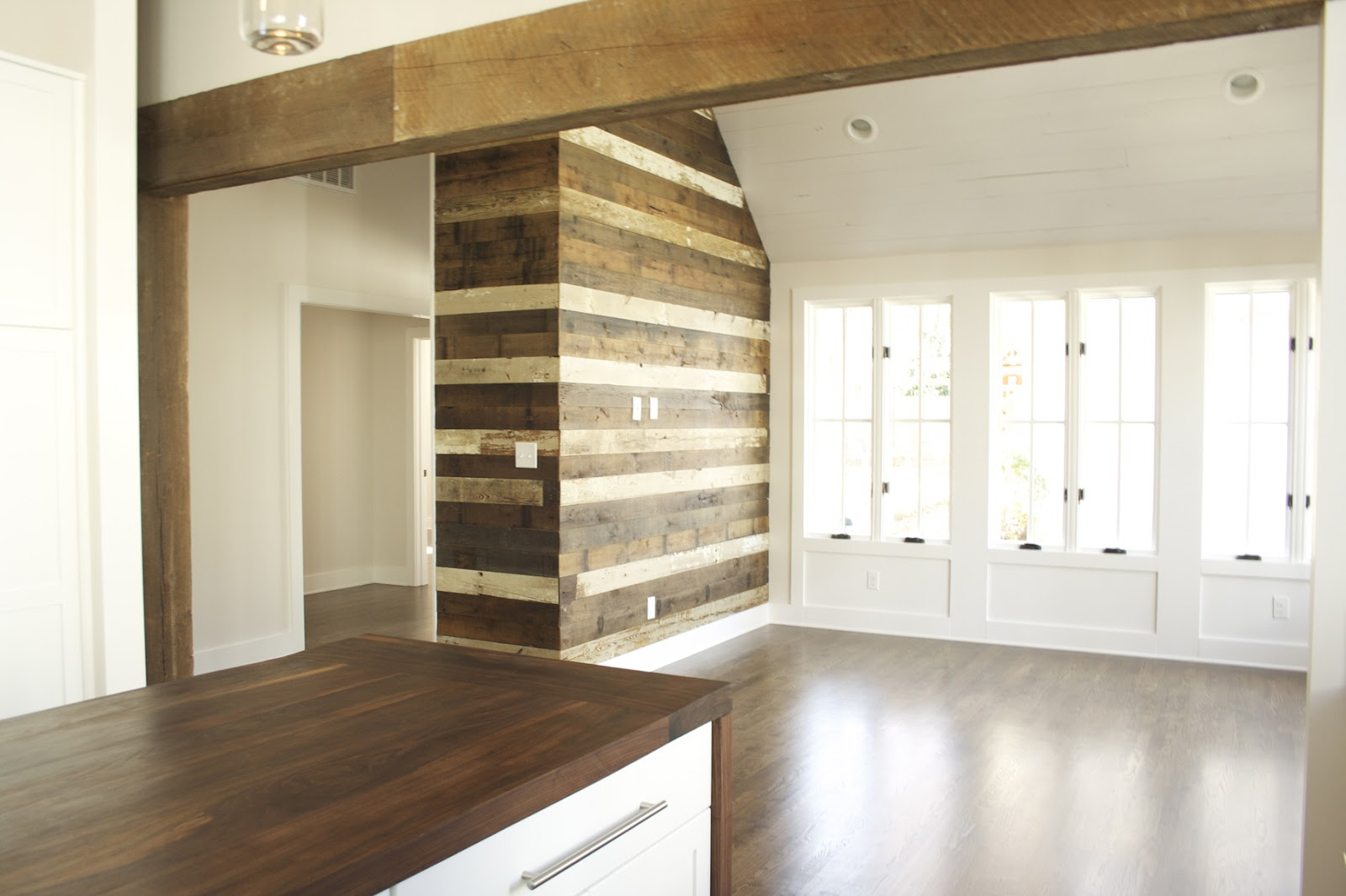 Reclaimed wood accent wall and antique beam room divider