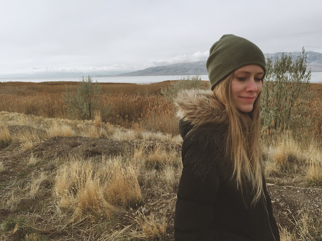 A blonde girl stands bundled up and smiling by a lake in the early winter. // THE JOY BLOG