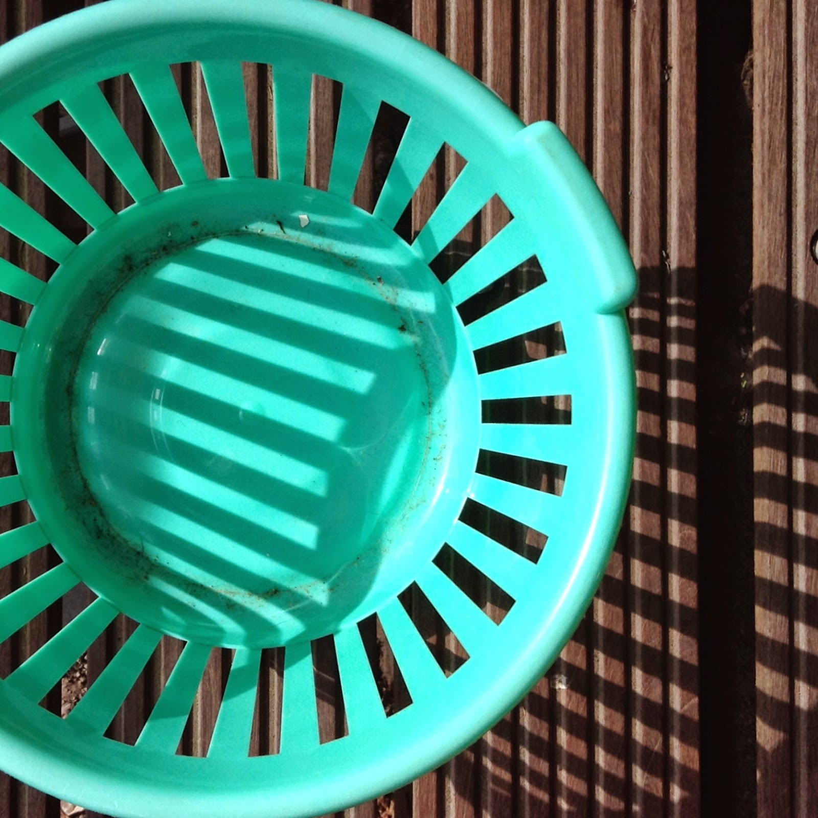 green laundry basket and its shadows