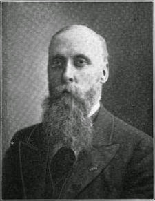 Early 20th century photo of a bald middle-aged white man with a long beard, dressed in a suit