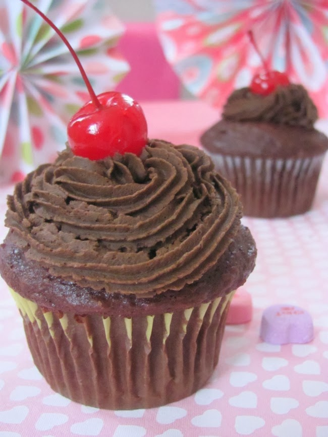 chocolate cupcakes with chocolate frosting and a cherry on top