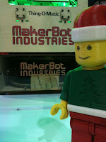 Lego-style figurine in front of MakerBot printer