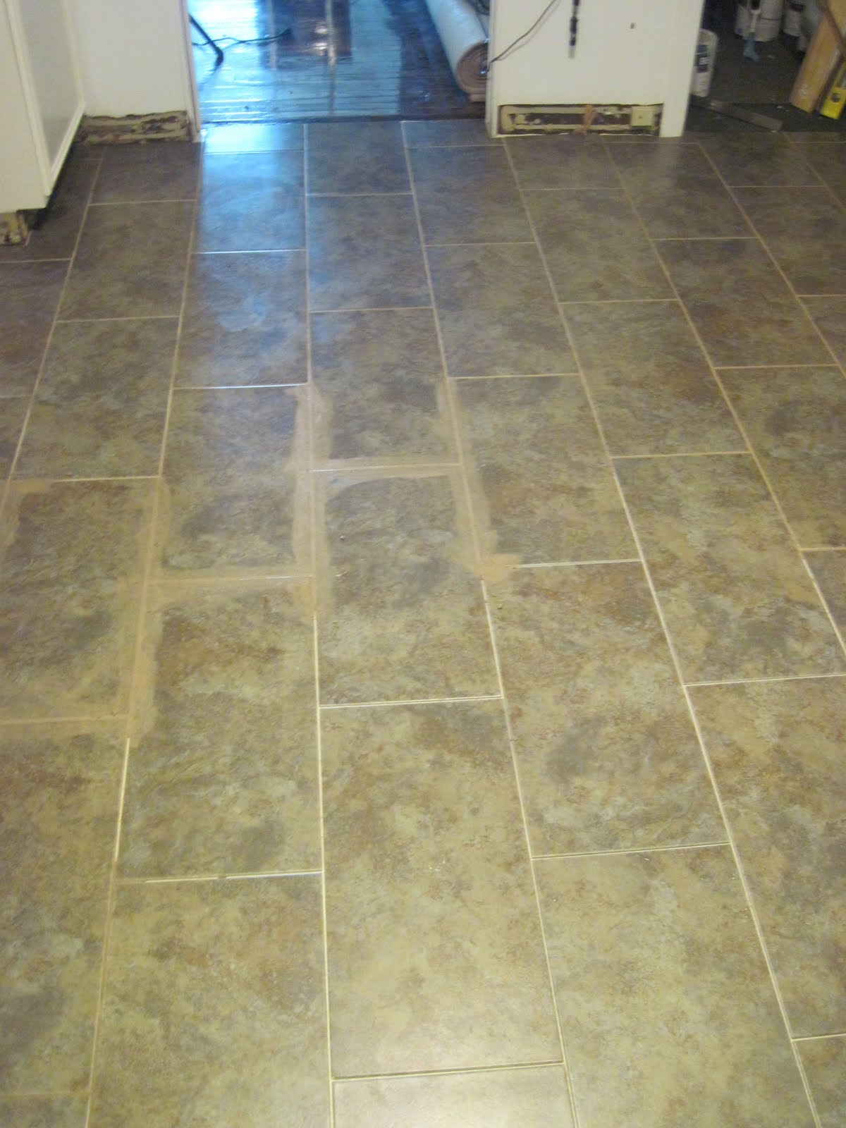 Our old abode kitchen floor groutable vinyl tile grouting the tiles with earth dailygadgetfo Image collections