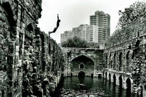 A boy jumping into the Black waters of the Baoli