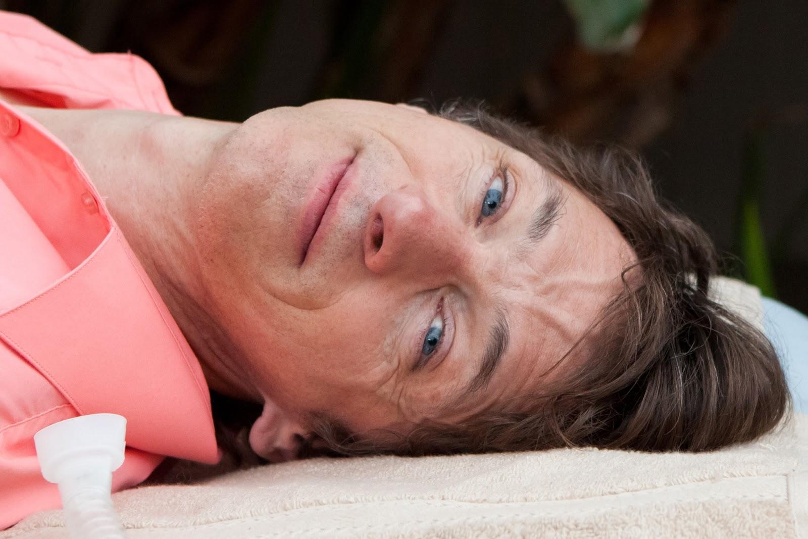 Mark, sdraiato sulla sua lettiga, il collo tutto all'indietro e la schiena inarcata, guarda lo spettatore con i suoi profondi occhi blu.