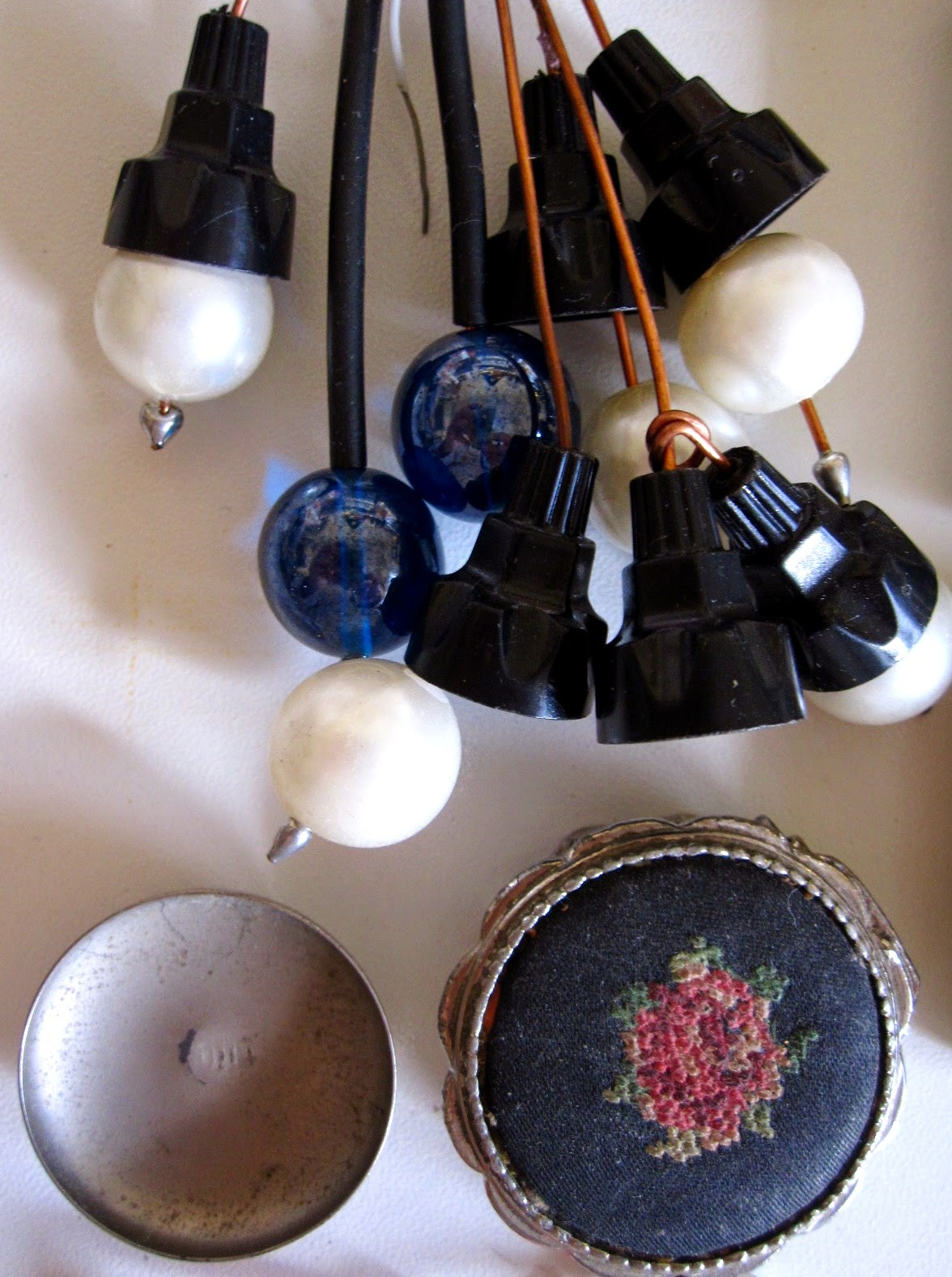 Collection of vintage plastic bits that could make modern miniature light fittings, plus a tiny embroidered box and a little round metal platter.