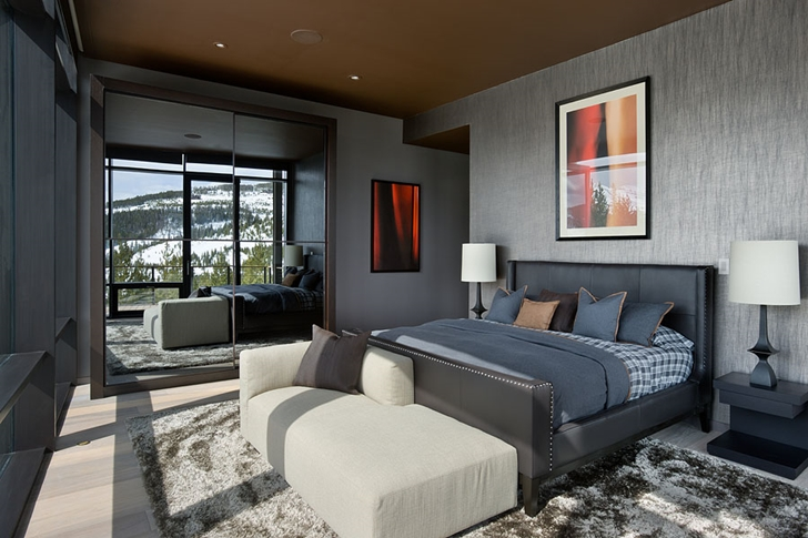 Modern dark bedroom in Elegant Mountain Home by Reid Smith Architects