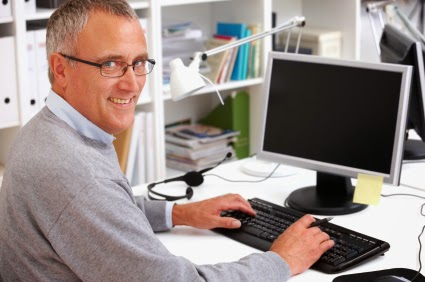 Man typing on computer and smiling at camera.