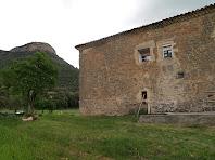 La façana de ponent de la casa d'els Quatre Vents amb el Turó de Sant Salvador al fons
