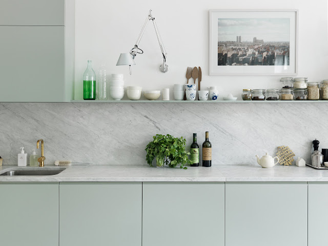 kitchen with gray green floating shelves, marble backsplash and counters, and brass faucet