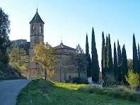 Les façanes de llevant i nord de l'església de Sant Genís d'Orís. Al fons, a l'esquerra de la imatge, el Castell d'Orís