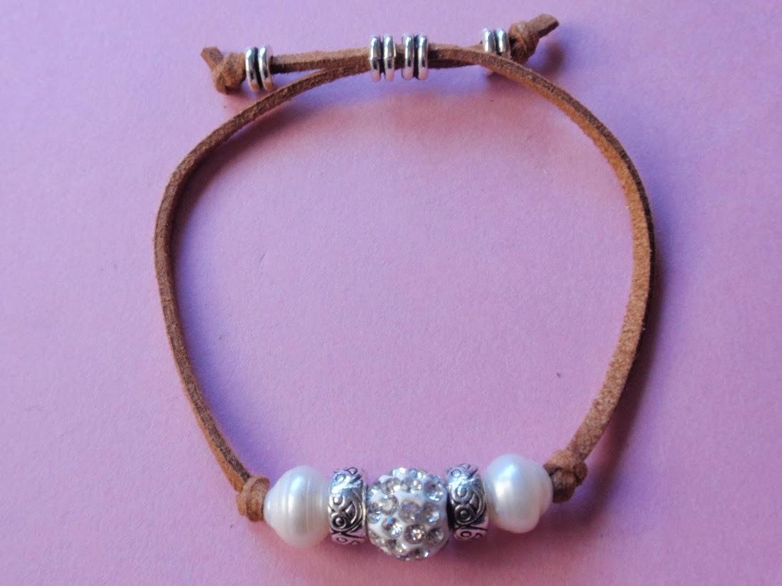 Pulsera ajustable en antelina color camel con cristal en tonos plateados en el centro y perlas de agua dulce a los lados.