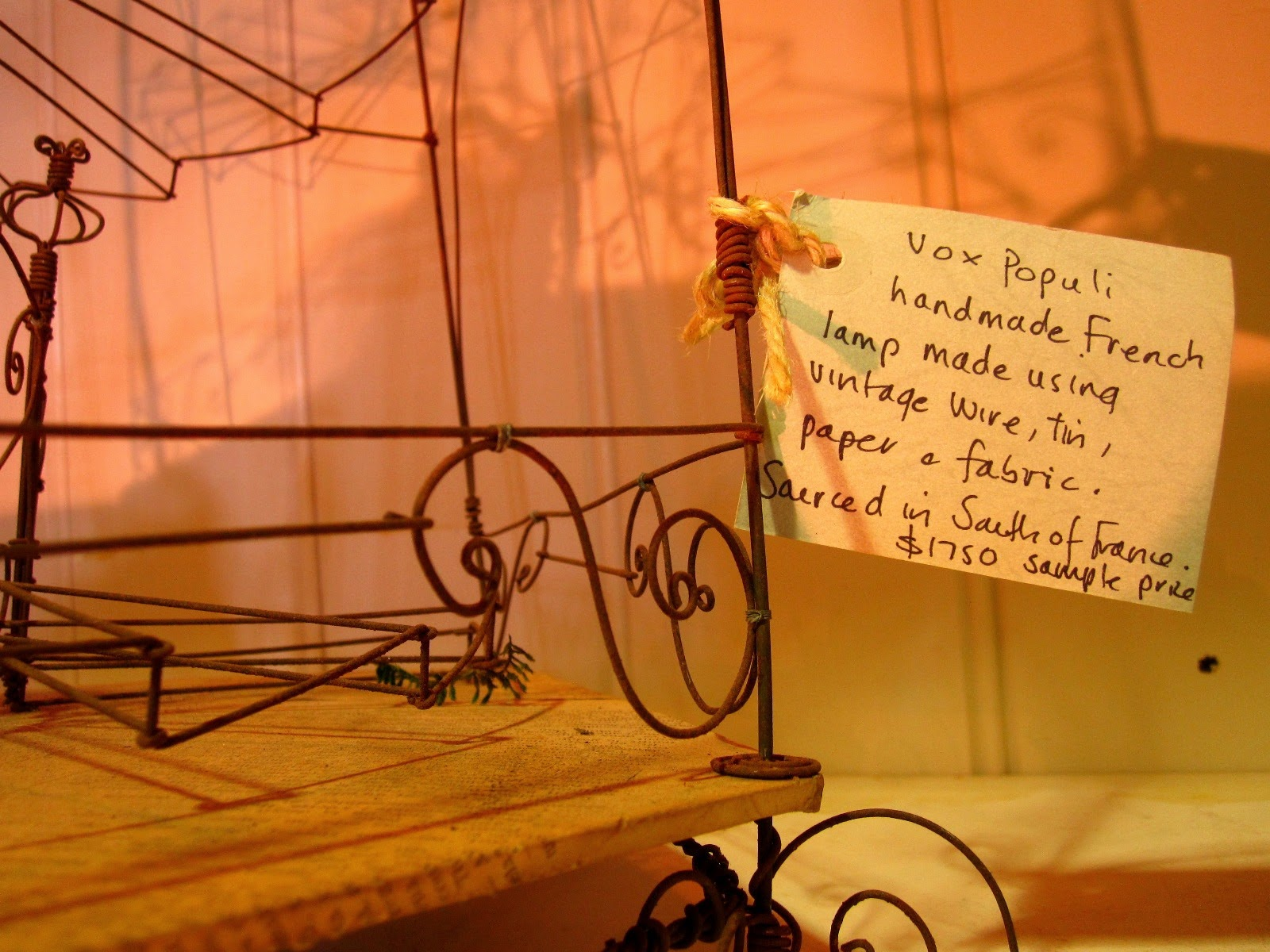 Price tag which reads 'Vox Populi handmade French lamp made using vintage wire, tin, paper and fabric. Sourced in South of France $1750 sample price.'