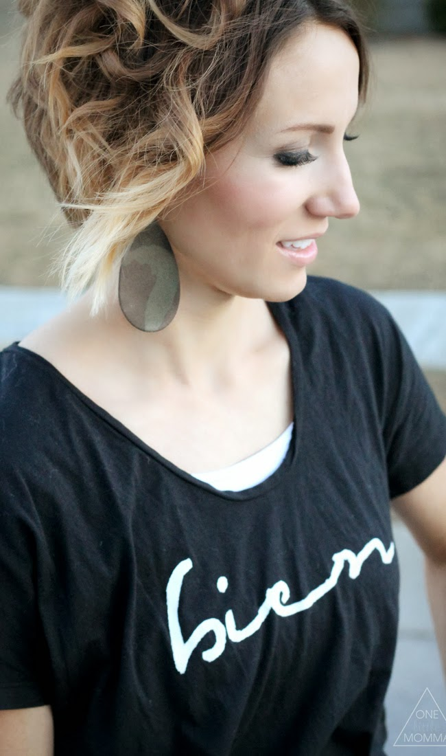 Black graphic tee and camo leather earrings