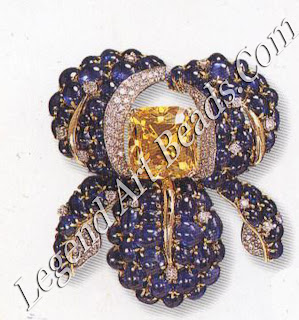 An iris brooch with a large 18 carat vivid yellow diamond and cabochon sapphires