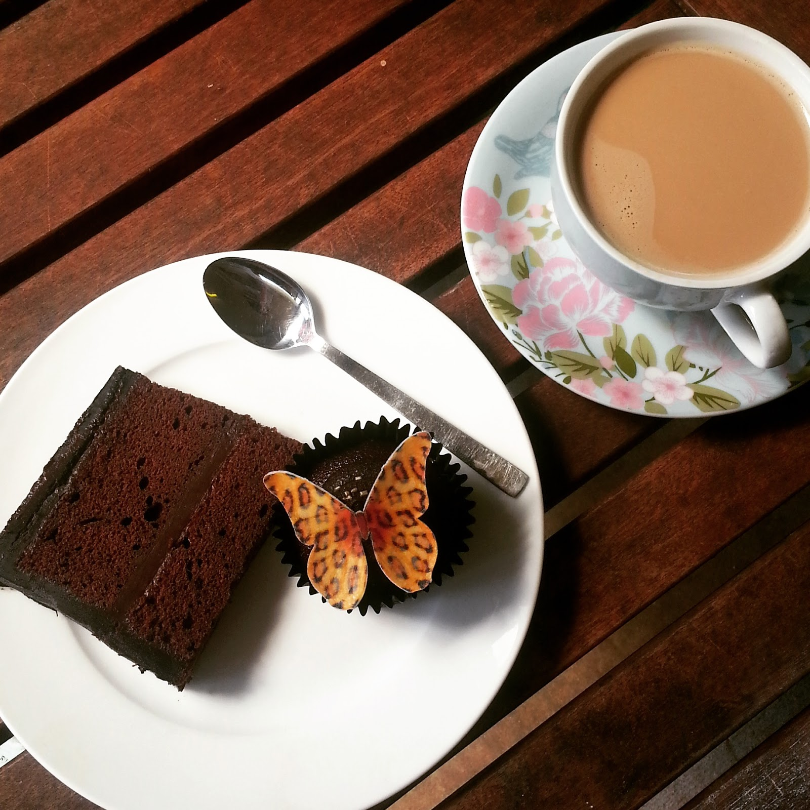 A slice of chocolate cakes, edible leopard print butterfly cupcake and a cup of nespresso coffee.