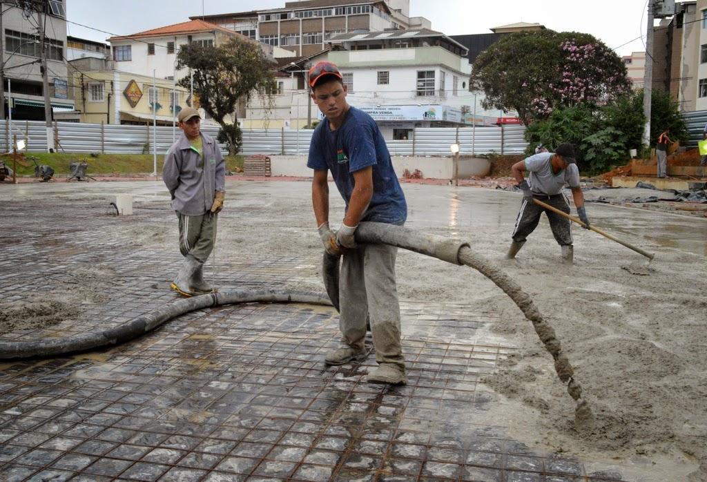 Operários fazem trabalho de concretagem na Praça Olímpica