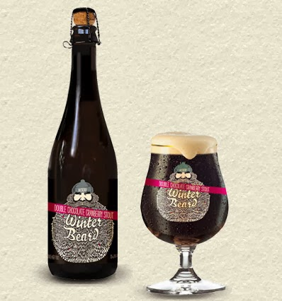 Bottle of dark stout with a beer chalice beside it showing off the thick beer foam on top.
