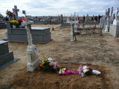 flores sobre una tumba de tierra con cruz de mármol blanco
