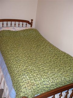 completed green twin-sized afghan spread out over a twin bed