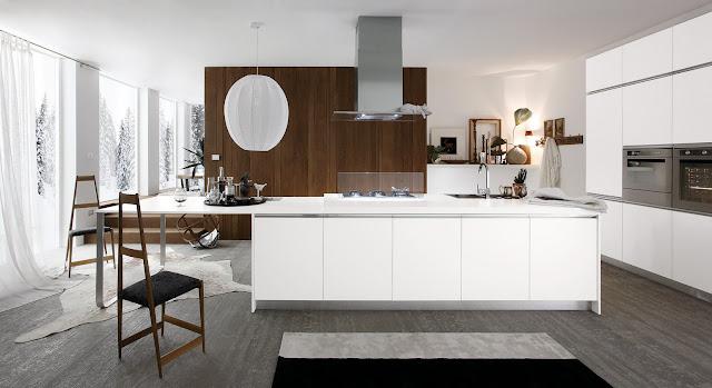 Cuisine design blanche avec îlot sans poignées. Mur d'armoire avec électroménager, coin repas en bout d'îlot. Cuisiniste Montpellier