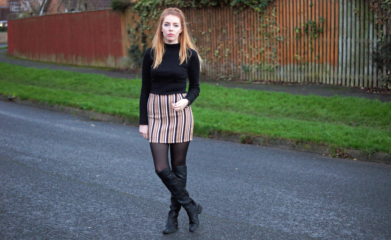 black turtle neck and camel skirt with over the knee boots