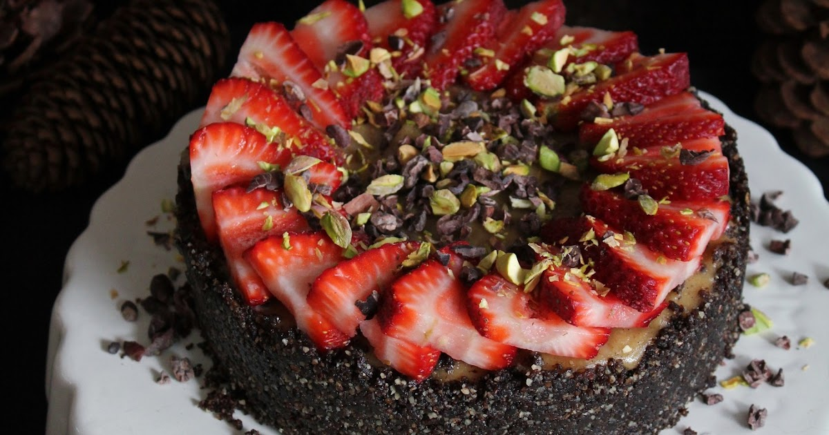 vanilla cheesecake with chocolate crust, strawberries, cacao nibs + pistachios
