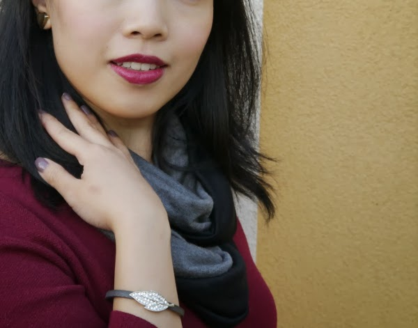 Details: grey-mauve nail polish, vampy lipstick, a sparkly bracelet, and gold stud earrings that look like shields.