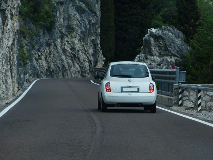 Coche blanco en carretera de montaña.